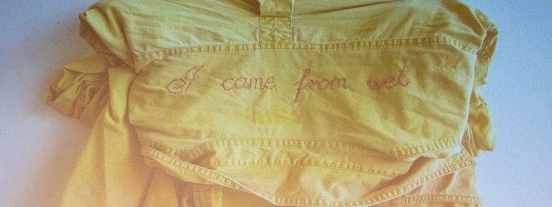 A yellow shirt embroidered on the back with the words