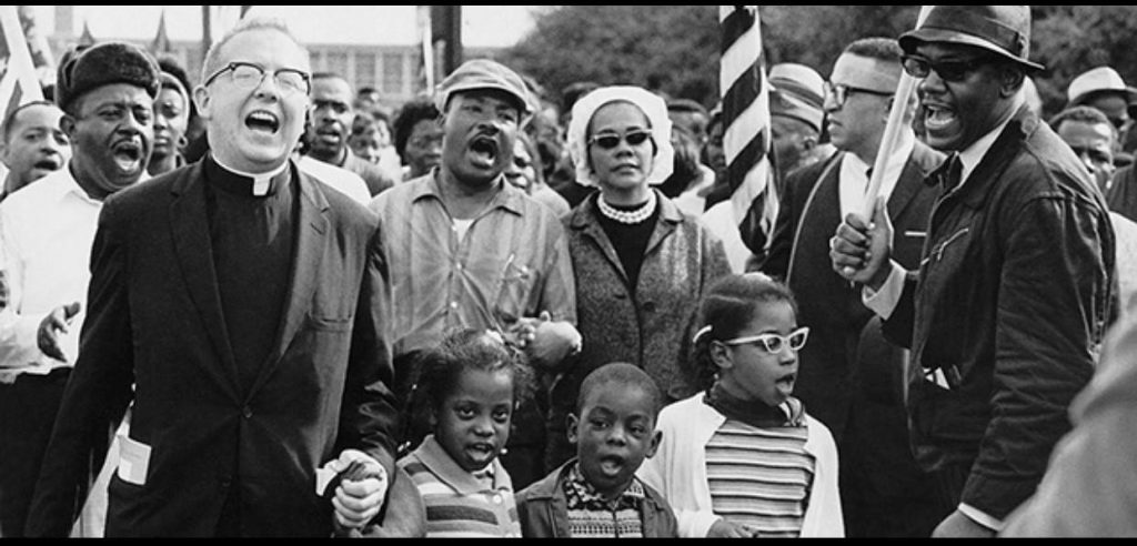 A group of protesters marching with Martin Luther King, including a White priest